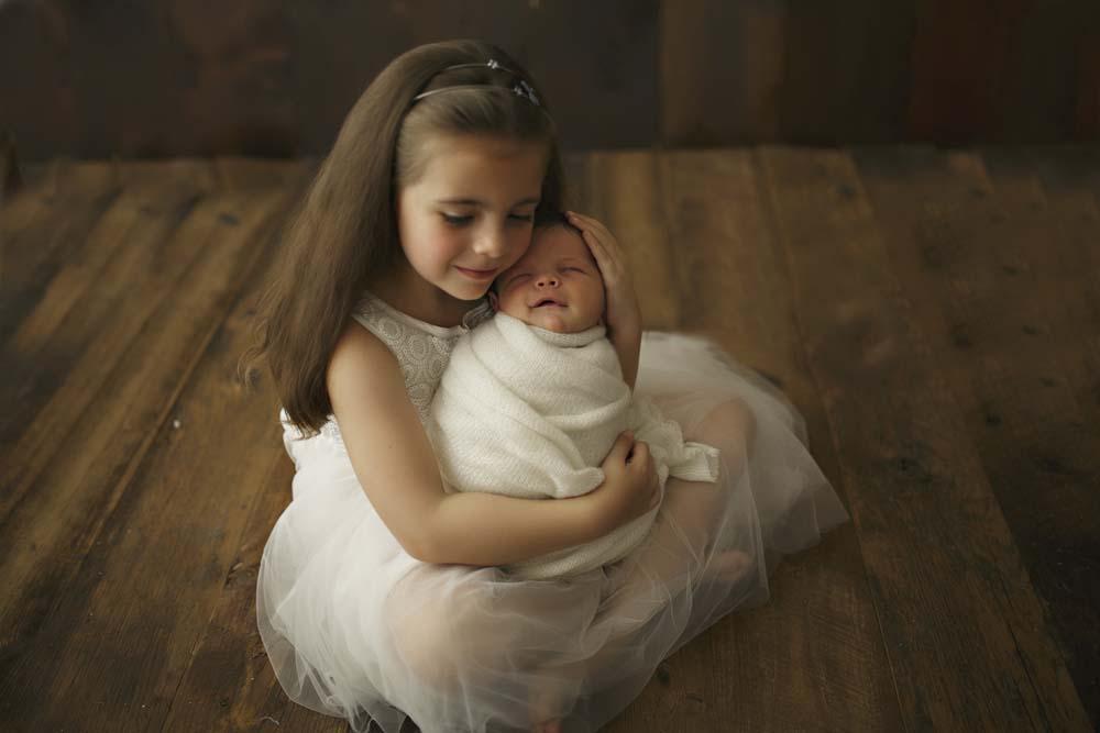 newborn with girl in dress